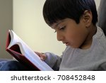 Kid Reading Book With Interest. ...