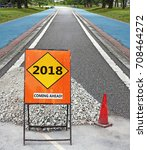 Small photo of A construction signage indicating Year 2018 coming ahead, on a road.