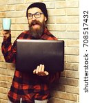 Small photo of Bearded man, long beard. Brutal caucasian smiling happy unshaven hipster holding laptop with mag or cup in red black checkered shirt with hat and glasses on beige brick wall studio background