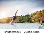 young man diving into a lake.... | Shutterstock . vector #708564886