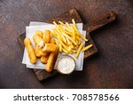 Small photo of Fish fingers and Chips british fast food with tartar sauce on dark background