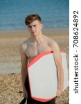 Teenage boy holding a body board on a beach - stock photo