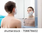 Young teenage boy shaving for the first time - stock photo