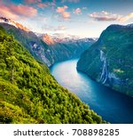 Splendid summer sunset of Sunnylvsfjorden fjord canyon, Geiranger village location, western Norway. Aerial evening view of famous Seven Sisters waterfalls. Beauty of nature concept background.