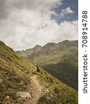 hiker along a trail in the alps ... | Shutterstock . vector #708914788