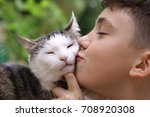 Stock photo happy boy hold cat smiling close up photo on the summer green garded background 708920308