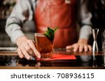Stock photo barman holds a cocktail with mint in his hand no face selective focus 708936115