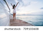 Luxury travel on the yacht. Young woman enjoying the sunset on boat deck sailing the sea. - stock photo