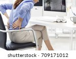 businesswoman with pain in back  | Shutterstock . vector #709171012
