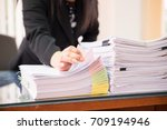 Small photo of Asian business woman office workers holding are arranging documents of unfinished documents on office desk,Stack of business paper,document management,Businesswoman examining documents