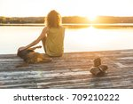 Small photo of Woman and dog relaxing on the dock at sunset. Autumn colors, unstaged situation with candid model and her dog. Relaxation and friendship concepts.