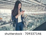 airport woman on smart phone at ... | Shutterstock . vector #709337146