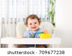 cute baby boy eating by himself ... | Shutterstock . vector #709677238