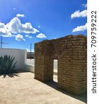 Small photo of Adobe Brick Arch Outside Blue Skies Puffy Clouds Agave West Texas Marfa