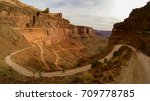 cyclists climb a winding dirt road up the steep cliff of Canyonlands national park - stock photo