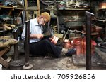 Small photo of SANLIURFA, TURKEY - JULY 01, 2010 : A coppersmith busily making a copper container in the Sanliurfa bazaar in eastern Turkey. Sanliurfa is also known as Urfa.