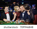 Happy guy was kissed by two beautiful girls after win in roulette - stock photo