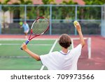 Small photo of Boy playing tennis on outdoor court. Teenager with tennis racket and ball in sport club. Active exercise for kids. Summer activities for children. Training for young kid. Child learning to play.
