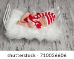 Baby In Santa's Costume With A...