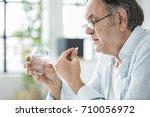 old man taking a pill | Shutterstock . vector #710056972