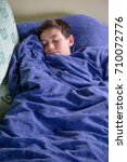 Unwell young teenage boy wrapped in a duvet on a sofa - stock photo