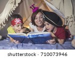 mother reading a fairy tale to... | Shutterstock . vector #710073946