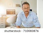 cheerful mature man sitting in... | Shutterstock . vector #710083876