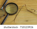Small photo of Conceptual image of business surveillance scrutiny oversight. Top view of 2 magnifying glasses and eyeglasses on wooden surface. Selective focus.