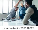 two colleagues giving high five ... | Shutterstock . vector #710148628