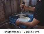 mid section of washing plates...   Shutterstock . vector #710166496