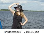 Small photo of A young girl in a black hat with fields and white coturas and a black short mini dress with strasses posing on the pantone (landing stage) of the Volga River. Russia.