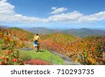 Couple embracing each other, standing on top of  mountain. Man with arms around his girlfriend looking at autumn landscape, on hiking trip. Close to Asheville, Blue Ridge Parkway, North Carolina, USA.