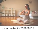 Small photo of Pregnant woman meditates indoor in yoga pose. Woman enjoying in meditation.