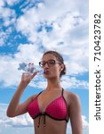 Girl wearing glasses in a bathing suit drinking water