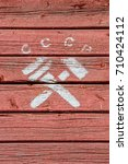 Small photo of The letters CCCP (russian abbreviation for USSR, Union of Soviet Socialist Republics) and a crossed hammer and monkey wrench, a communist symbol, painted in white on a red, weathered, wooden surface.