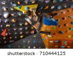 young woman bouldering in... | Shutterstock . vector #710444125