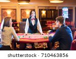 Small photo of Cute lady casino dealer at poker table. Happy couple is playing Black Jack.