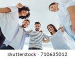 joyful positive team standing... | Shutterstock . vector #710635012