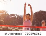 Small photo of Happy female athlete with arms raised crossing finish line on sunny dy