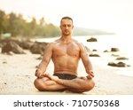 guy doing yoga on the beach in... | Shutterstock . vector #710750368