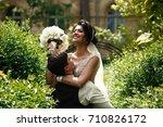 groom holds bride up standing... | Shutterstock . vector #710826172