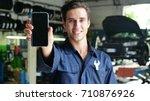 in a car garage a mechanic... | Shutterstock . vector #710876926