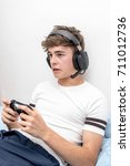 Small photo of Teenage boy playing a video game