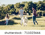 Stock photo beautiful happy family is having fun with golden retriever outdoors mother father and daughter 711025666