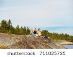 family sitting on rock by lake | Shutterstock . vector #711025735