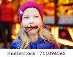 adorable little girl eating... | Shutterstock . vector #711096562