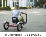 A little boy riding a tricycle...