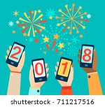 hands with mobiles showing 2018.... | Shutterstock .eps vector #711217516