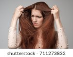 Small photo of Pretty caucasian woman trying to comb hair.