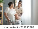 Smiling nurse helping senior...